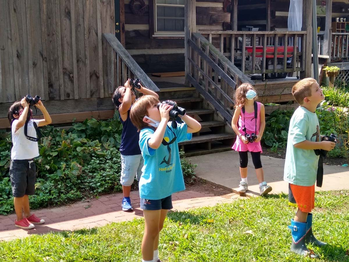 Young children look up into the sky with binoculars
