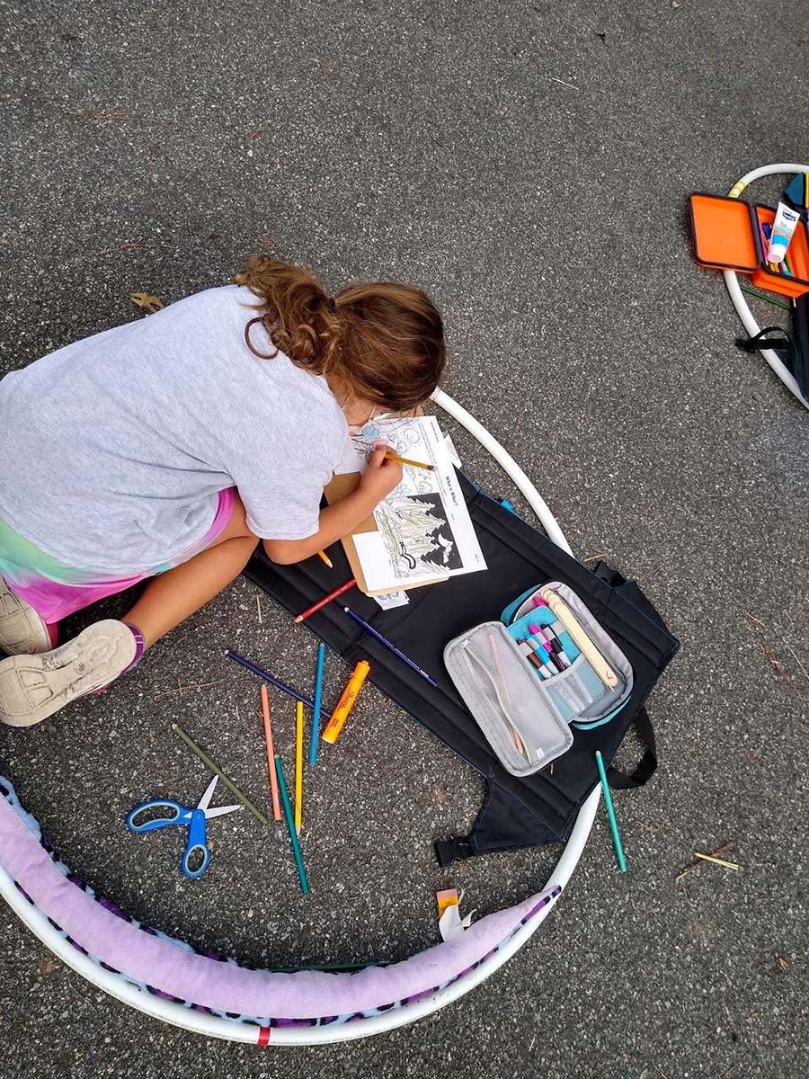 A student kneels on the ground in a hula hoop, working on a drawing