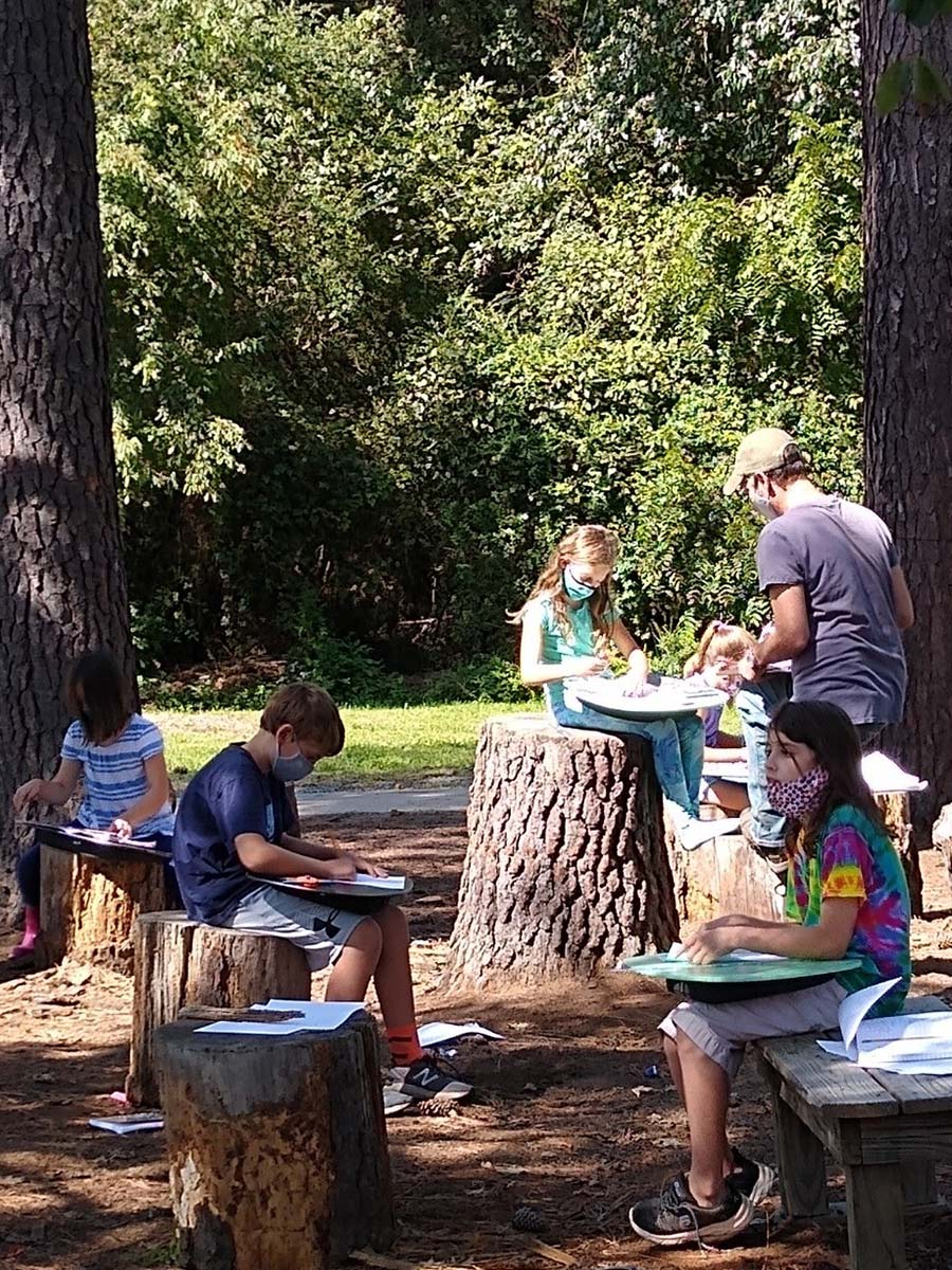 Students and teacher working outdoors under trees, wearing masks