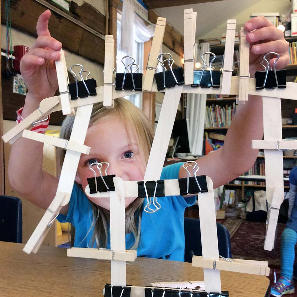 first grade girl building with popsicle stick and binder clips