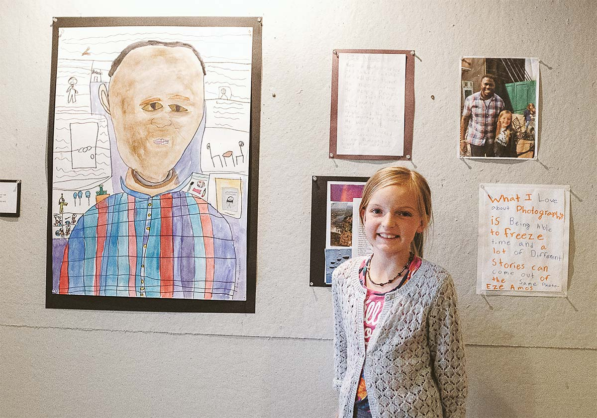 Student poses with her portrait of a Change Maker