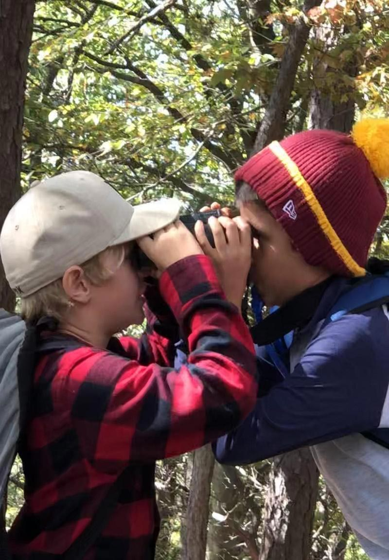 Two students spying each other through binoculars