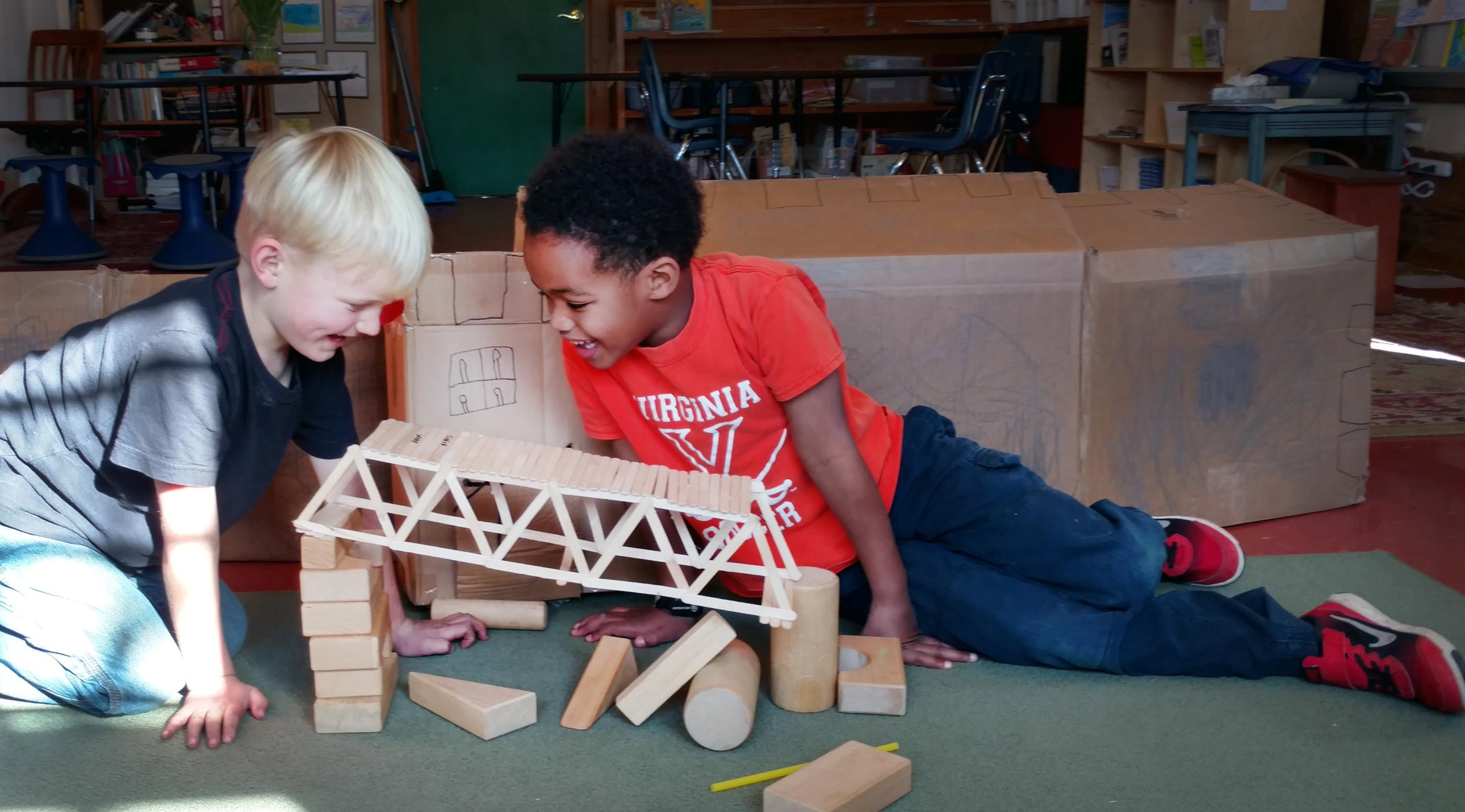 Young students smile over a construction of wooden sticks