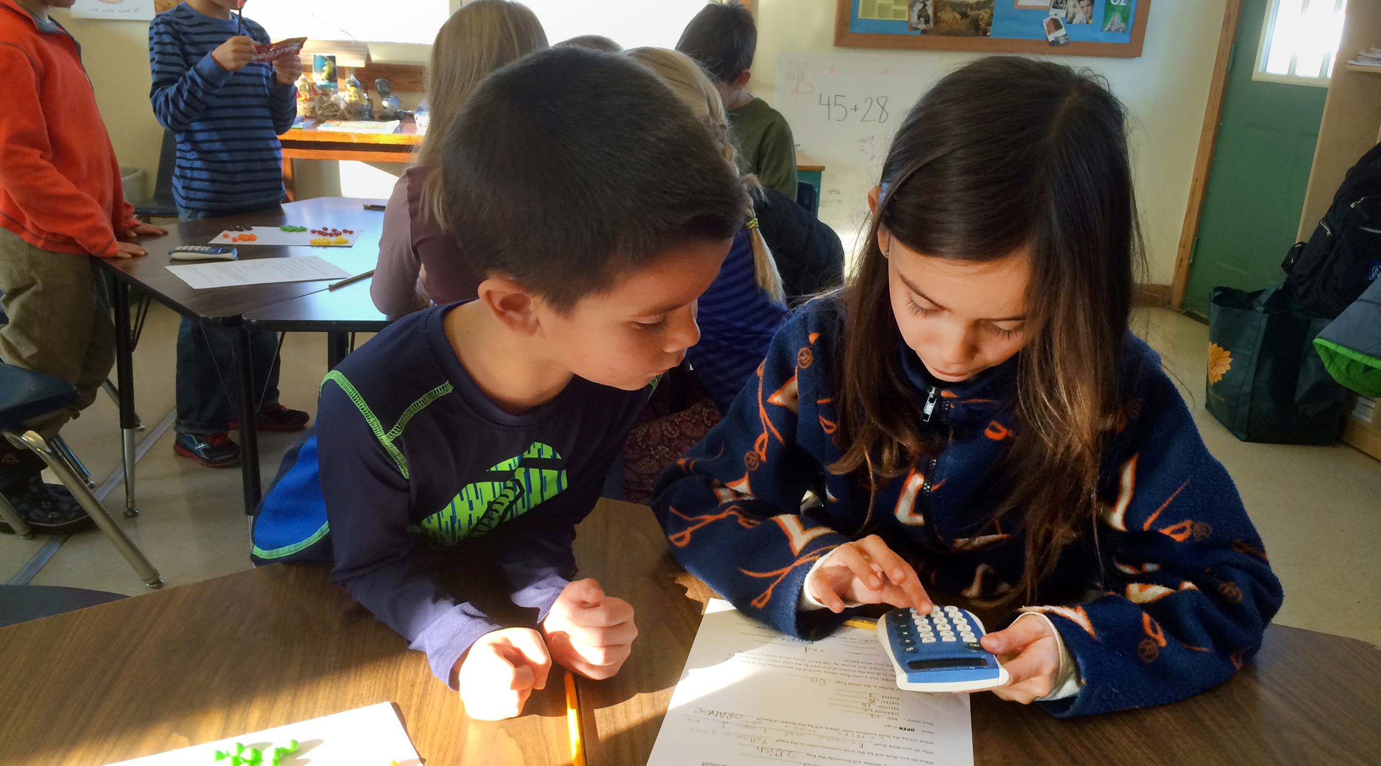 Two students work together on math using a calculator and candies