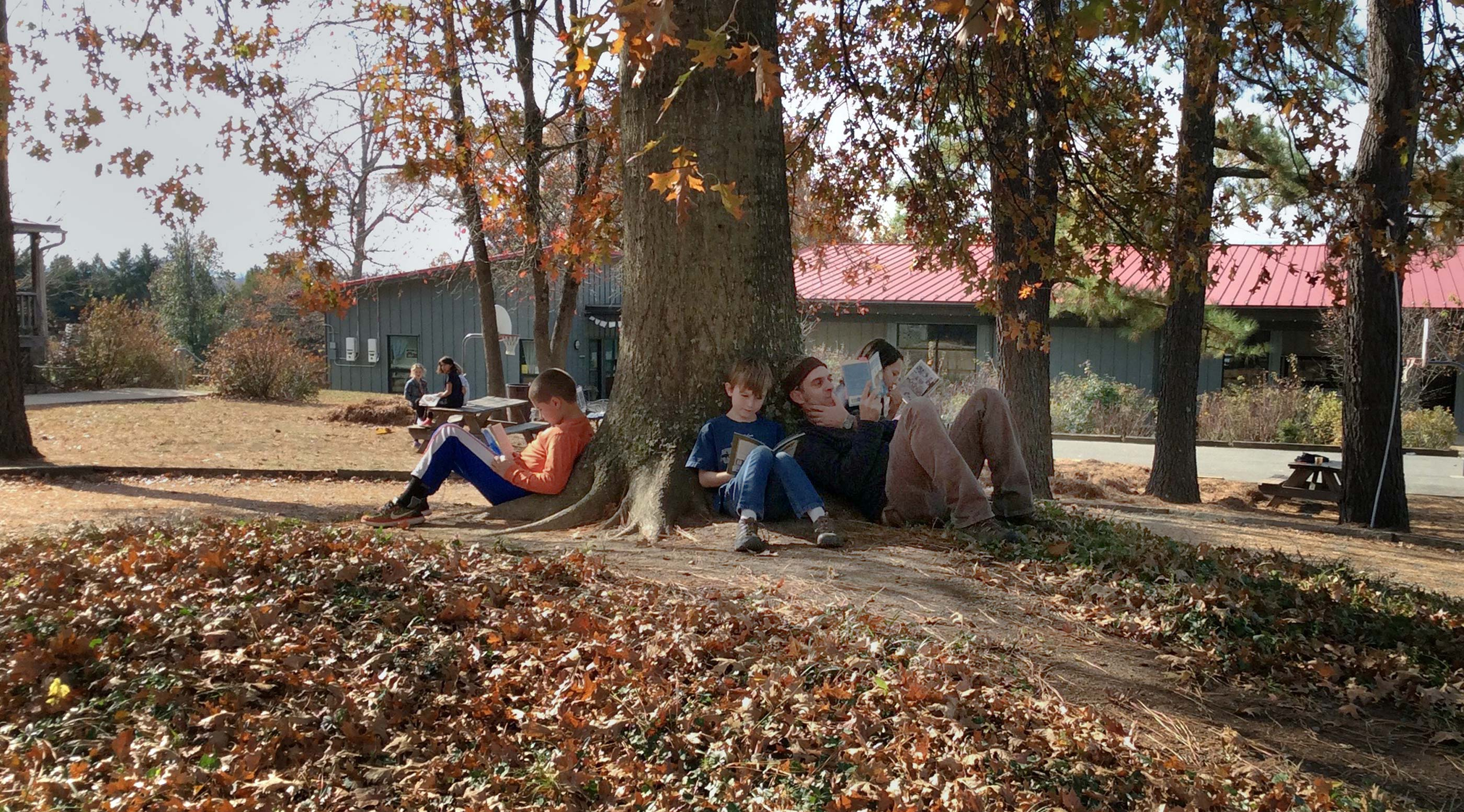 Students and their teacher read together under a tree