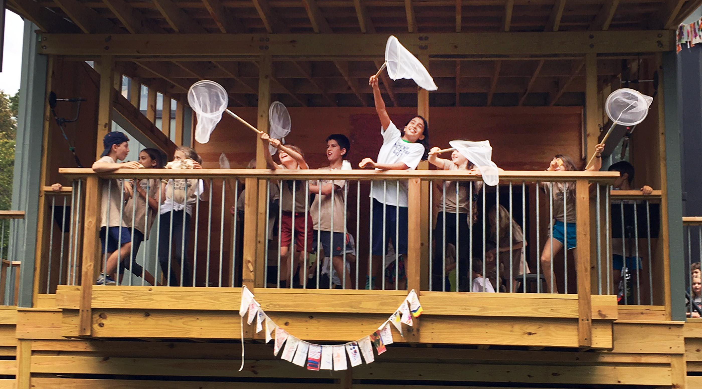 Group of students wave butterfly nets excitedly on the outdoor classroom deck