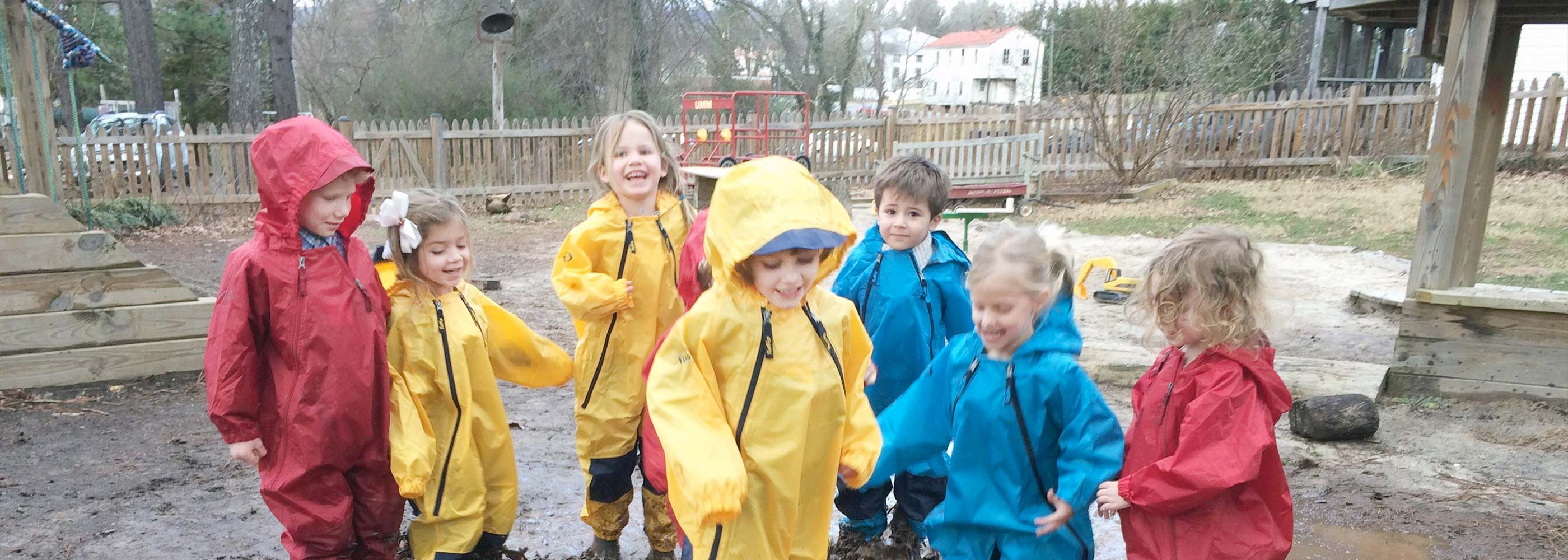 Preschoolers in rain gear laugh and stomp in a mud puddle